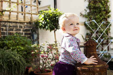 Baby girl standing while leaning on garden lantern LANG_EVOIMAGES
