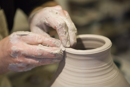 moulding: Close up of male potters hands shaping clay pot on pottery wheel in workshop LANG_EVOIMAGES