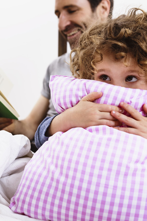 storybook: Girl hugging pillow while father reads storybook in bed