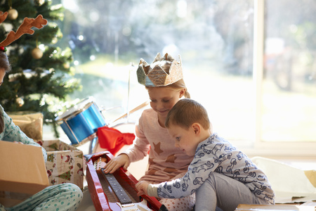 nightwear: Girl and brother on living room floor looking at toy guitar christmas gift