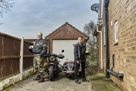 sidecar: Portrait of senior male motorcyclist with grandson by motorcycle and sidecar