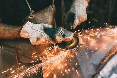 Handen van metaalbewerker slijpen koper in forge workshop Stockfoto - 87366874