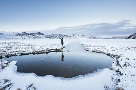 Man standing at waters edge,looking at view,Kleifarvatn,Iceland