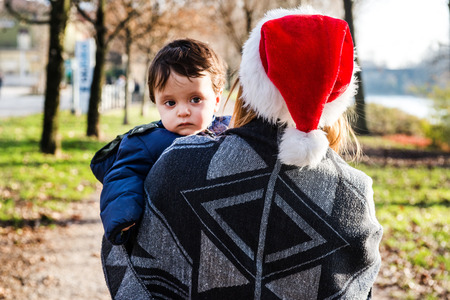 Over shoulder view of young woman in santa hat carrying baby boy in park