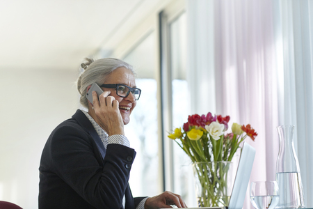 aging woman: Senior businesswoman making smartphone call at home