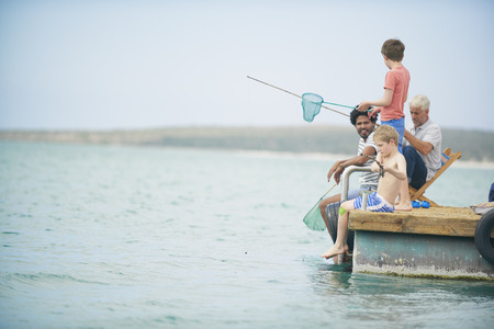 only boys: Family fishing on houseboat deck,Kraalbaai,South Africa