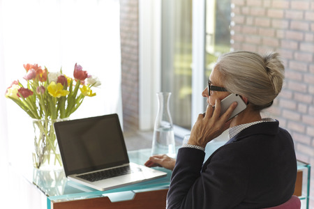 aging woman: Senior businesswoman using laptop and making smartphone call at home desk LANG_EVOIMAGES