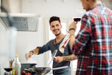 age 25 30 years: Male couple preparing meal together in kitchen,drinking wine