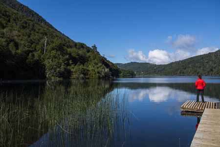 getting out: Woman enjoying the view of a calm lake in the South Chilean Lake district,Pucon,Chile LANG_EVOIMAGES