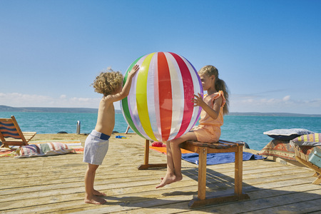 Boy and girl playing with beach ball on houseboat sun deck,Kraalbaai,South Africa LANG_EVOIMAGES