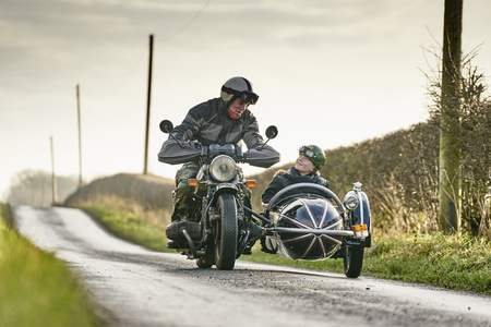 Senior man and grandson riding motorcycle and sidecar along rural road Stock Photo - 87367346