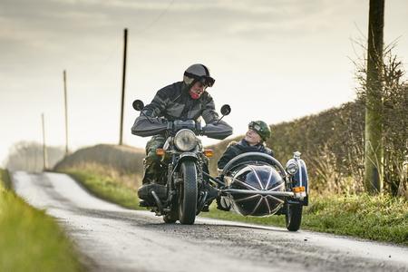 Senior Mann und Enkel Reiten Motorrad und Beiwagen entlang der Landstraße Lizenzfreie Bilder - 87367346