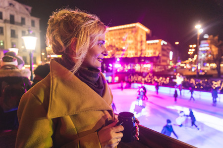 Woman watching ice skating from christmas market at night,Munich,Germany LANG_EVOIMAGES