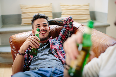 age 25 30 years: Male couple relaxing on sofa,holding beer bottles,laughing