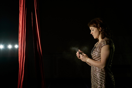 Young female aerial acrobat by silk rope looking at smartphone