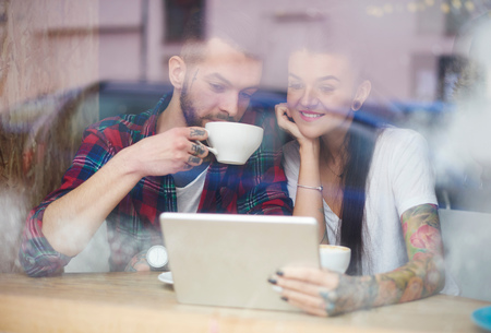 shop window: View through window of couple in coffee shop using digital tablet