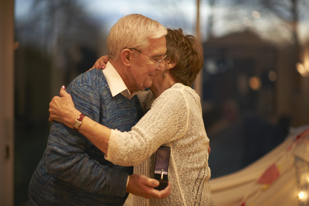 aging woman: Romantic senior couple hugging while holding gift box