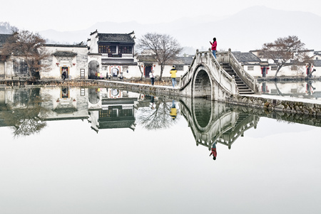 Mirror image of traditional houses and footbridge over lake,Hongcun Village,Anhui Province,China
