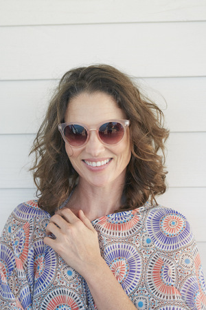 Portrait of woman wearing sunglasses looking at camera smiling