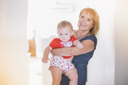 65 69 years: Portrait of senior woman carrying baby granddaughter at home
