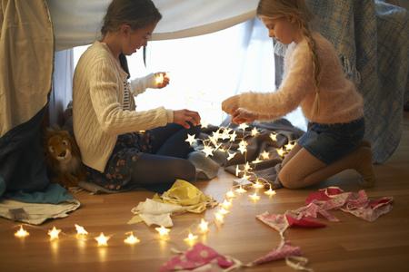 skirts: Two sisters in bedroom den preparing star shape lights