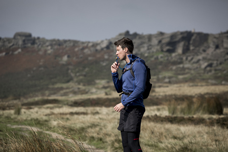 man drinking water: Male runner drinking from tube at Stanage Edge,Peak District,Derbyshire,UK LANG_EVOIMAGES