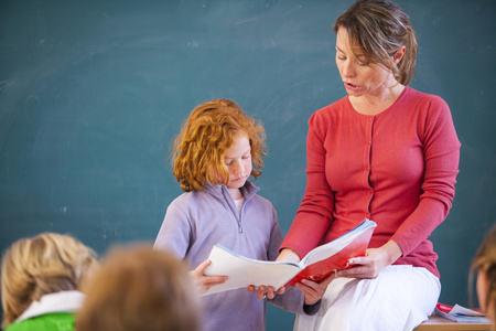 Primary schoolgirl reading book at front of classroom
