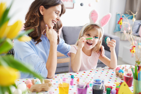 children painting: Woman and daughter painting easter eggs at table