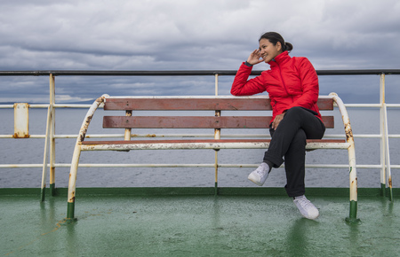 Woman sitting on ship-deck passing the Patagonian fjords,Chile