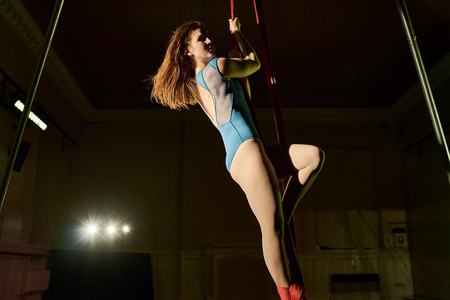 Waist down view of young female aerial acrobat climbing silk rope
