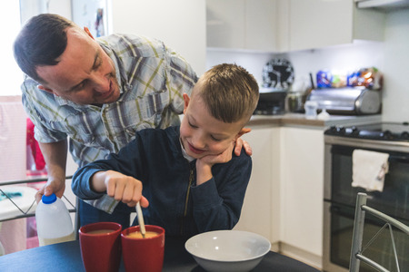 Father and son in kitchen,son stirring hot drink