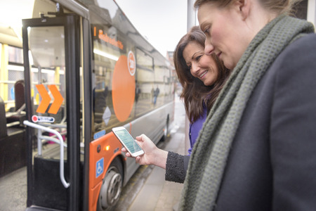 Passengers using smart phone to look at bus timetable before boarding electric bus