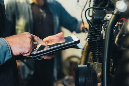 Two mature men,working in garage,using digital tablet,close-up LANG_EVOIMAGES