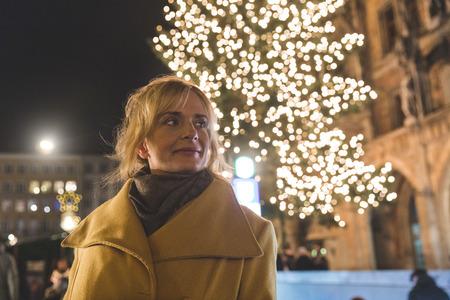 Woman waiting by illuminated christmas tree at night,Munich,Germany