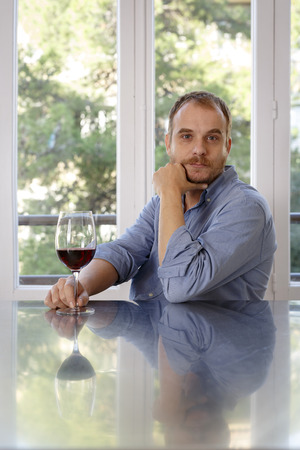 Man at home,sitting at table,holding glass of wine,pensive expression