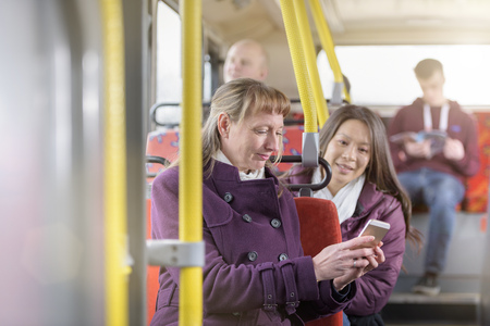 Passengers looking at smartphone on electric bus
