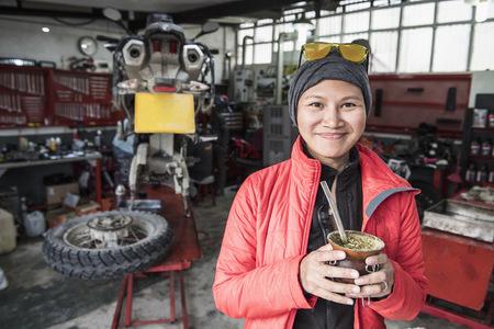 Portrait of woman drinking mate tea in motorbike mechanics workshop,Rio Grande,Tierra del Fuego,Argentina