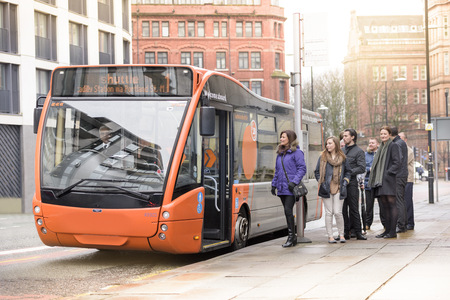 Passengers at bus stop waiting to board electric bus