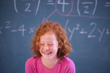Portrait of cute primary schoolgirl giggling in classroom LANG_EVOIMAGES