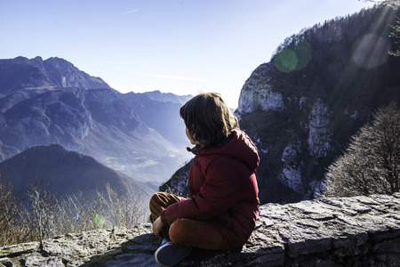 Boy sitting on wall looking out at mountain landscape,Italy LANG_EVOIMAGES