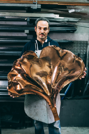 Portrait of male metalworker holding copper product,forge storeroom