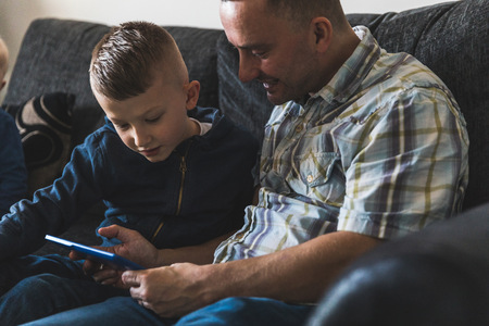 Father and son sitting on sofa,looking at digital tablet