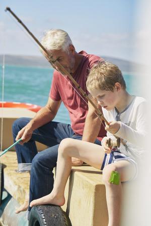 Grandfather and grandson fishing on houseboat sun deck,Kraalbaai,South Africa