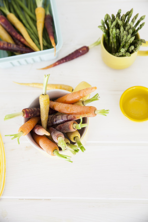 Overhead view of fresh colourful carrots and asparagus on kitchen table LANG_EVOIMAGES
