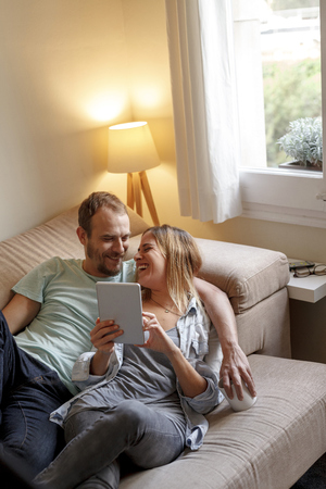 Mid adult couple relaxing on sofa,looking at digital tablet