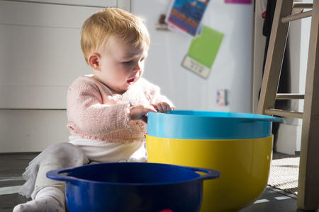 skirts: Baby girl sitting on kitchen floor playing with bowls