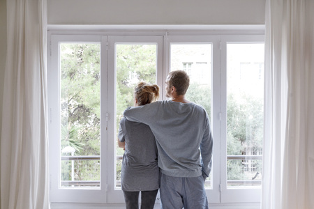 Mid adult couple at home,looking out of window,man hugging woman,rear view LANG_EVOIMAGES