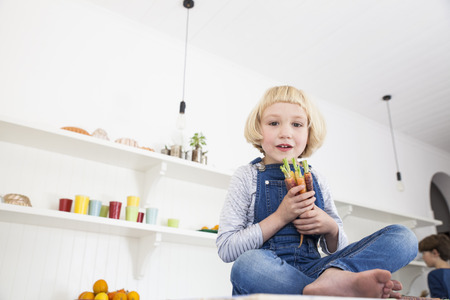 Portrait of cute girl sitting on kitchen counter holding bunch of colourful carrots