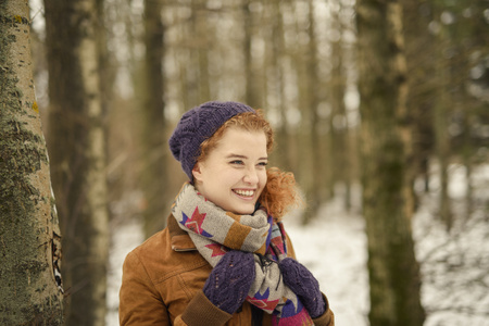 Portrait of woman in forest,wearing hat and scarf