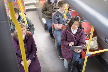 Passenger using digital tablet on electric bus,high angle view
